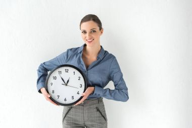 businesswoman holding wall clock in hands