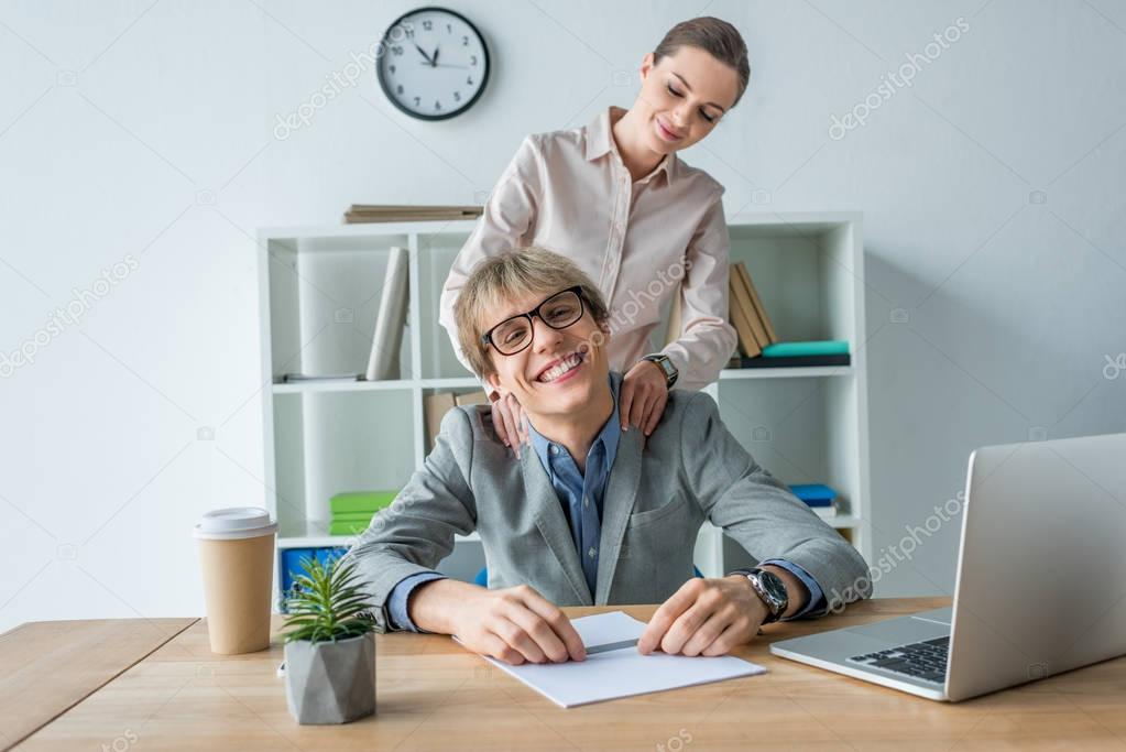 Businesswoman massaging shoulders to colleague at office