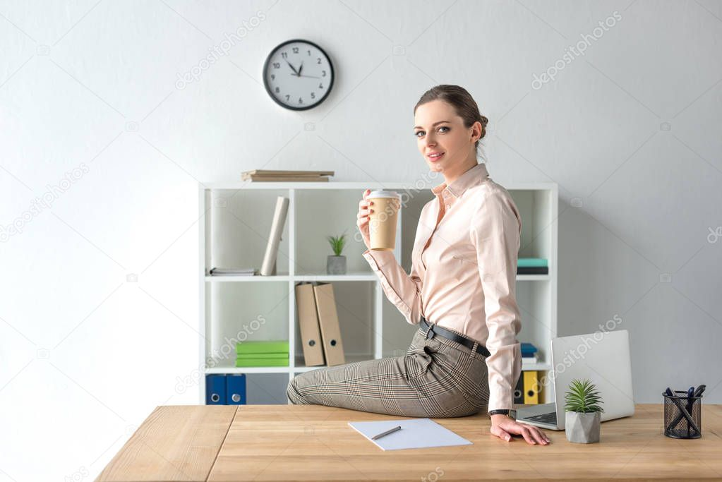 Businesswoman sitting on table with coffee