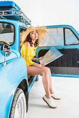 Térképet autóban ülő nő