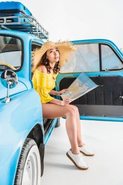 woman sitting in car with map