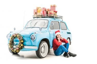 woman near car with christmas gifts