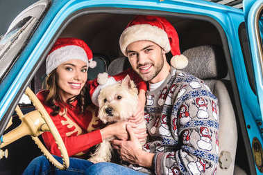 family in santa hats with dog in car