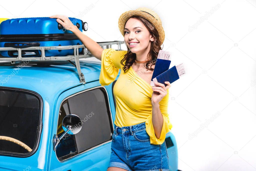 Smiling young woman with light tickets next to vintage car isolated on white stock vector