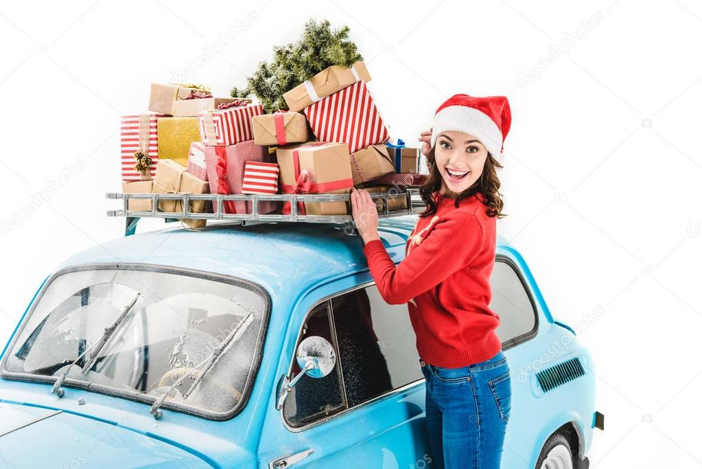 woman with christmas gifts on car roof