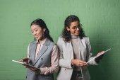 africké americké a asijské podnikatelky pomocí digitálních tablety před zelená stěna