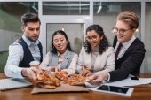 smiling multiethnic businesspeople eating pizza in office