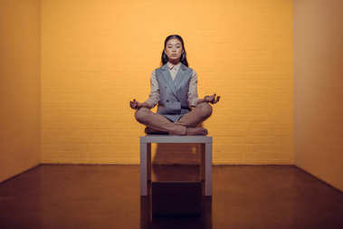 asian businesswoman meditating on table in front of orange wall