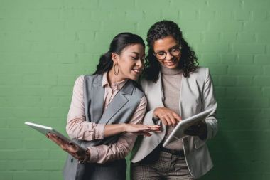 smiling african american and asian businesswomen working with digital tablets in front of green wall