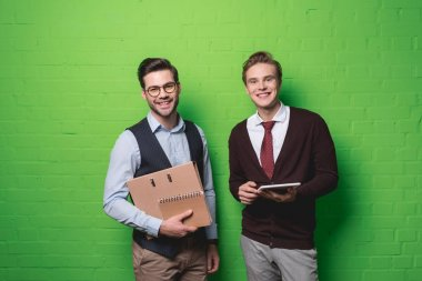 young smiling businessmen with digital tablet and documents in front of green wall