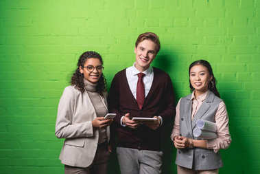young multiethnic businessman and businesswomen with gadgets and blueprints in front of green wall