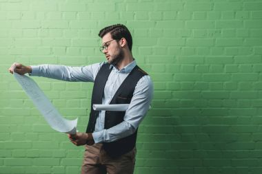 young concentrated businessman with blueprints in front of green wall