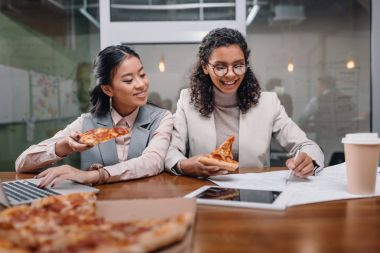 multiethnic businesswomen eating pizza and working in office