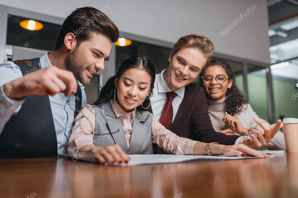smiling multiethnic businesspeople working with documents in office