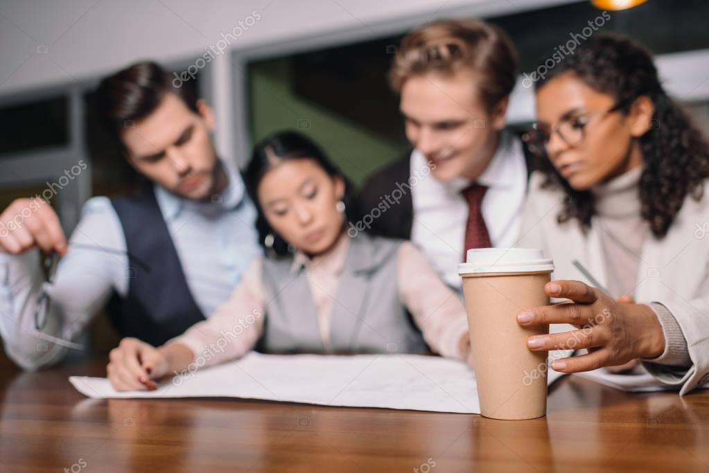 selective focus of multiethnic business team with coffee and documents working in office