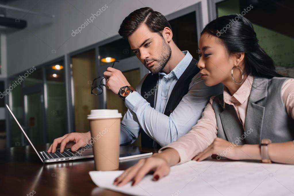 businessman and asian businesswoman working together with laptop and documents in office