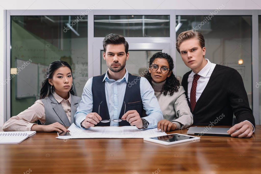 multicultural businesspeople with digital devices and paperwork in office
