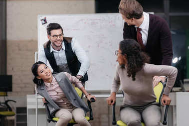 multiethnic businessmen and businesswomen have fun with swivel chairs in office