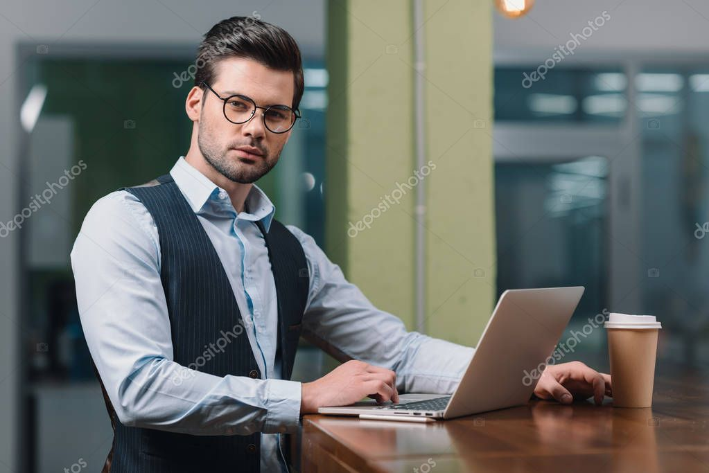 young businessman in eyeglasses working with laptop