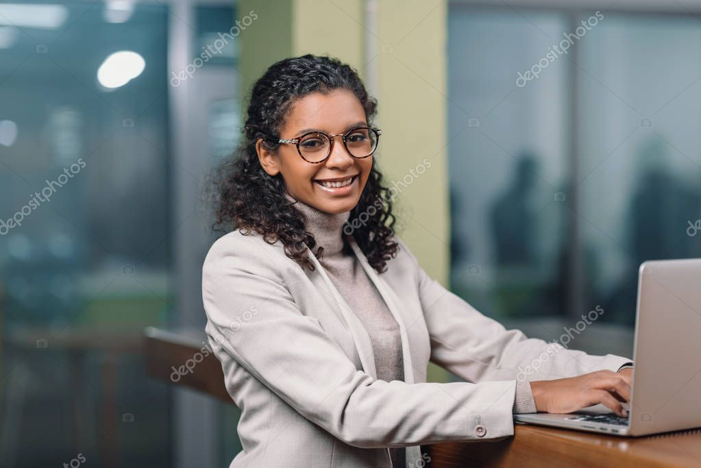 young smiling african american businesswoman in eyeglasses working with laptop
