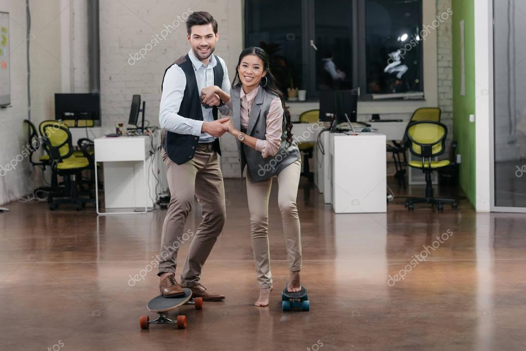multiethnic businesspeople have fun with skateboards in office