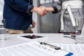 business partners shaking hands with contract on table on foreground
