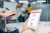 podnikatel držení tabletu s Instagramem na obrazovce v moderní kanceláři a kolega poznámky