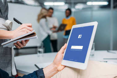 businessman holding tablet with facebook on screen at modern office while colleague making notes