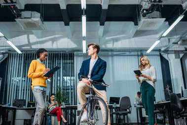 young businessman with bike at modern office with partners standing around
