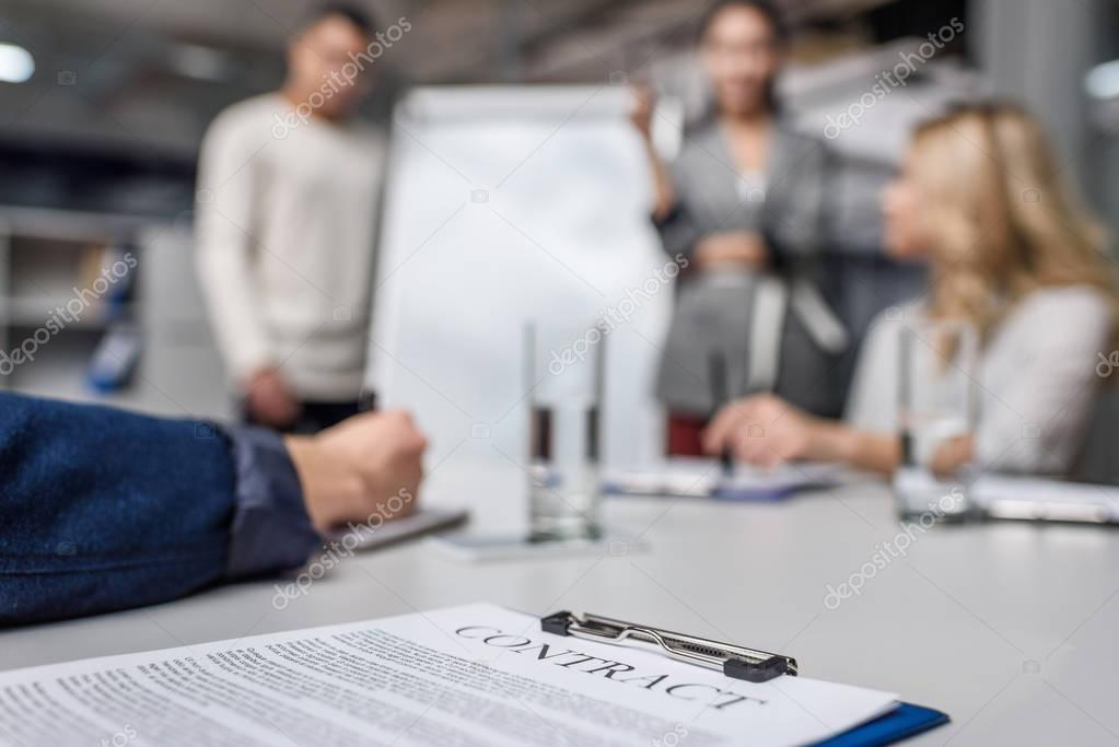 business contract on table with blurred businesspeople on background