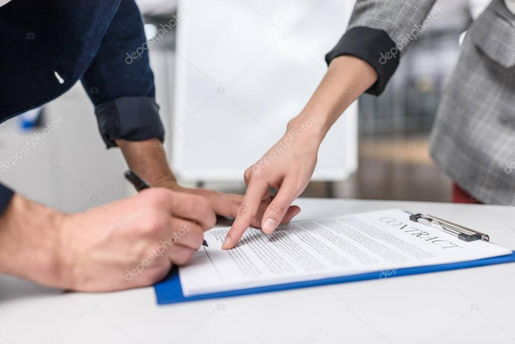 close-up shot of businessman signing contract while manageress pointing at it