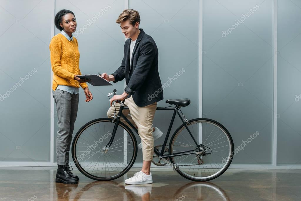 young businessman signing contract in hands of young african american colleague while he sitting on bike