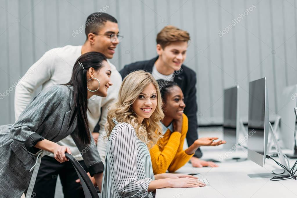 multiethnic managers looking at computer together in modern office