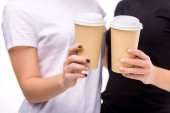 Fotografie partial view of women holding coffee to go in hands isolated on white