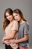 portrait of beautiful twin sisters hugging each other and looking at camera isolated on grey