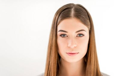 headshot of beautiful young woman with straight hair looking at camera isolated on white