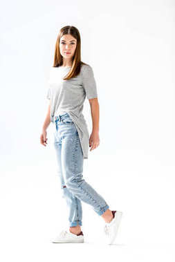 young stylish woman in jeans and grey shirt looking at camera,  isolated on white