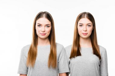 portrait of young smiling twins in grey tshirts looking at camera isolated on white