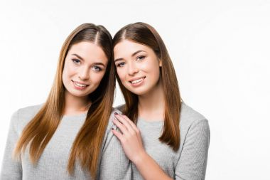 portrait of young smiling twins leaning on each other and looking at camera isolated on white