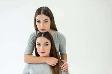 portrait of beautiful woman hugging twin sister and looking at camera