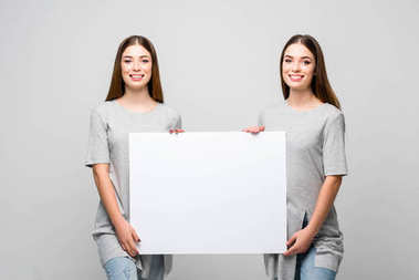 portrait of beautiful smiling twins holding blank banner in hands isolated on grey