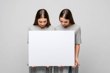 portrait of young twins looking at blank banner in hands isolated on grey