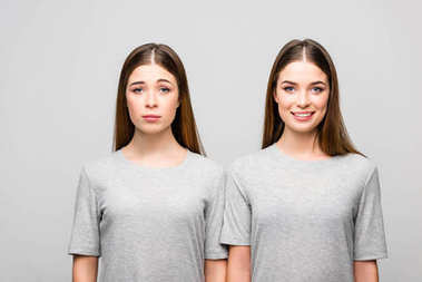 portrait of twin sisters in grey tshirts showing emotions isolated on grey