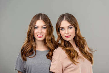 portrait of beautiful smiling twin sisters isolated on grey