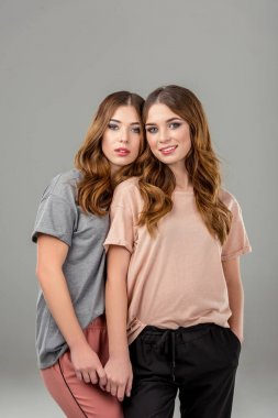 portrait of beautiful twin sisters in stylish clothing isolated on grey