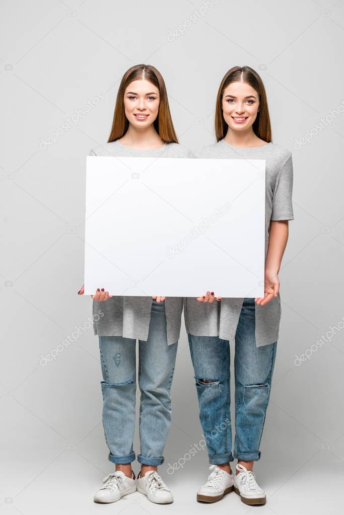 beautiful smiling twins holding blank banner in hands isolated on grey