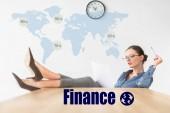 Fotografia Donna di affari lettura di documenti e che si siede con le gambe sul tavolo con iscrizione di finanza e mappa del mondo