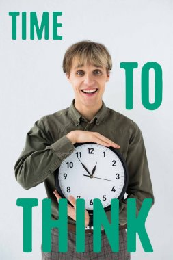 Smiling businessman holding wall clock in hands on white with time to think inscription