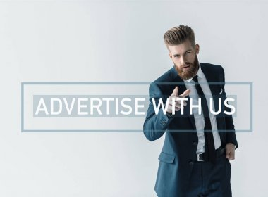 Handsome bearded businessman in stylish suit pointing at camera with finger. Business inscription on wall
