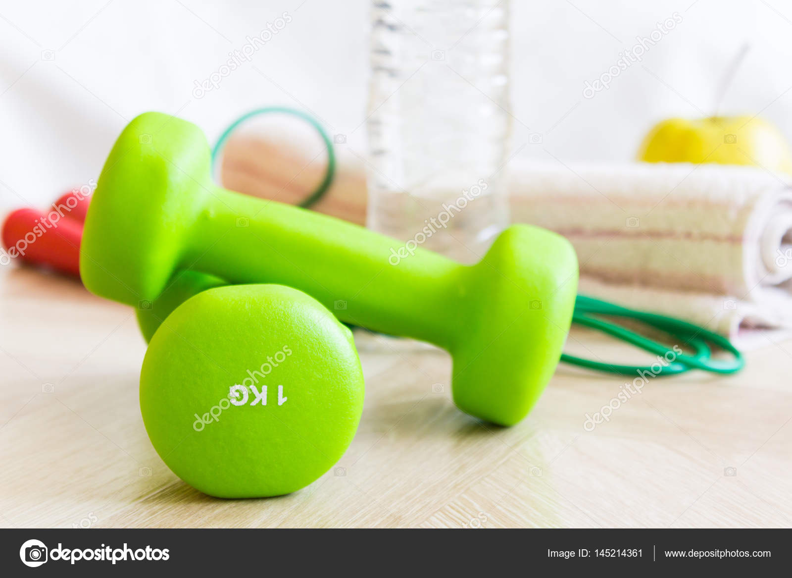 Green dumbbells, water bottle, apple, jump rope and a towel